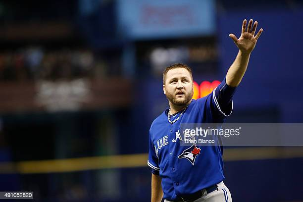 Pitcher Mark Buehrle of the Toronto Blue Jays gestures to the cheering crowd after being taken off the mound by manager John Gibbons during the...