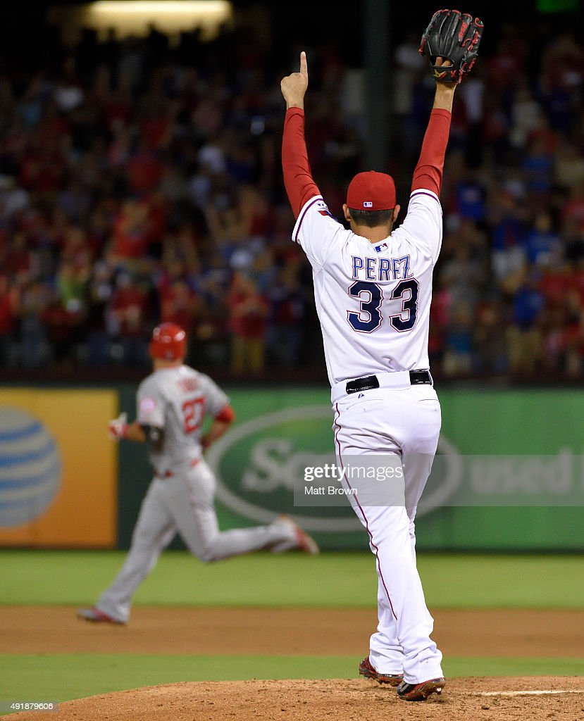 Pitcher Martin Perez #33 of the Texas Rangers reacts as a deep hit by <a gi-track='captionPersonalityLinkClicked' href=/galleries/search?phrase=Mike+Trout&family=editorial&specificpeople=7091306 ng-click='$event.stopPropagation()'>Mike Trout</a> #27 of the Los Angeles Angels of Anaheim is caught during the sixth inning of the game at Globe Life Park in Arlington on October 2, 2015 in Arlington, California.