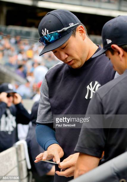 Pitcher Masahiro Tanaka of the New York Yankees goes through Topps baseball cards in the dugout on Topps National Baseball Card Day before an MLB...