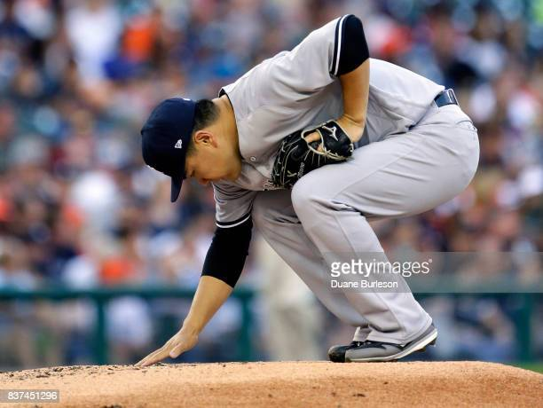 Pitcher Masahiro Tanaka of the New York Yankees grooms the mound before pitching against the Detroit Tigers during the first inning at Comerica Park...