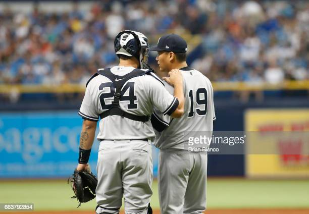 Pitcher Masahiro Tanaka of the New York Yankees has a conversation on t he mound with catcher Gary Sanchez after giving up a sacrifice fly to Evan...