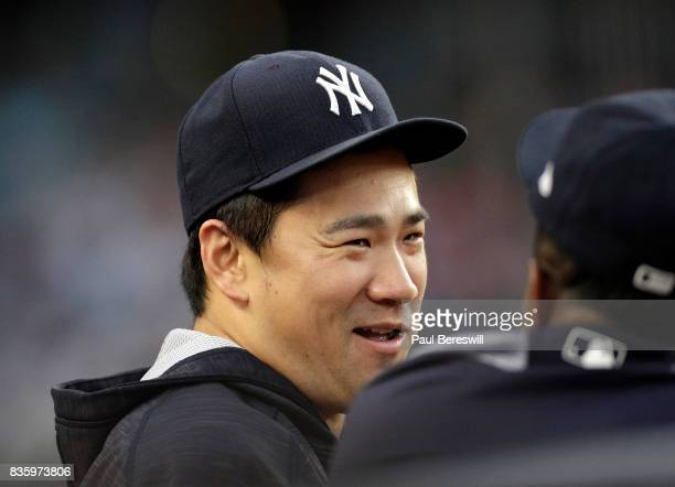 Pitcher Masahiro Tanaka of the New York Yankees talks with teammates during an MLB baseball game against the New York Mets on August 14 2017 at...