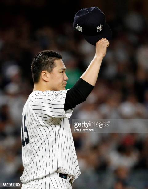 Pitcher Masahiro Tanaka of the New York Yankees tips his cap to teammate Aaron Judge who reached above the wall in right field to rob Francisco...