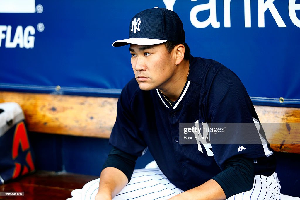 Pitcher Masahiro Tanaka of the New York Yankees waits in the dugout before starting a spring training game against the Atlanta Braves on March 12...