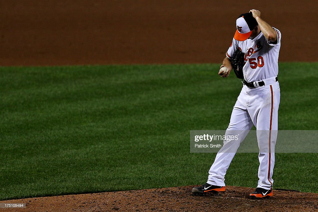 Pitcher Miguel Gonzalez #50 of the Baltimore Orioles reacts after giving up a grand-slam, hit by Jason Castro #15 of the Houston Astros (not pictured), in the fourth inning at Oriole Park at Camden Yards on July 31, 2013 in Baltimore, Maryland. The Houston Astros won, 11-0.