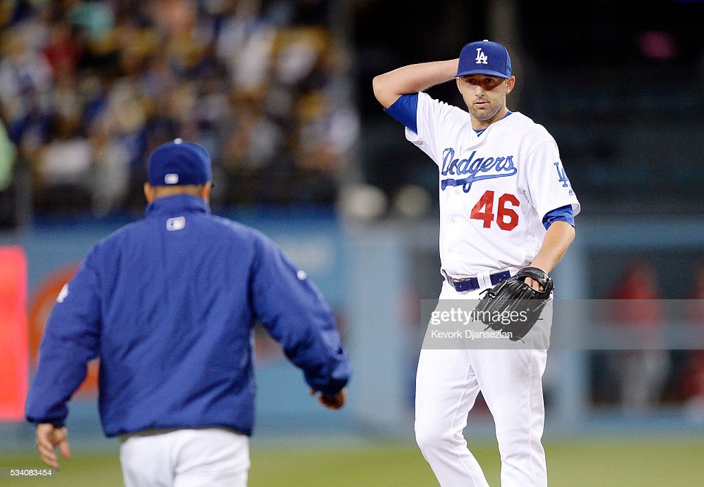 Pitcher Mike Bolsinger #46 of the Los Angeles Dodgers looks at manager Dave Roberts #30 as walks up to the mound to replace him against the Cincinnati Reds during the sixth inning of the baseball game at Dodger Stadium May 24, 2016, in Los Angeles, California.