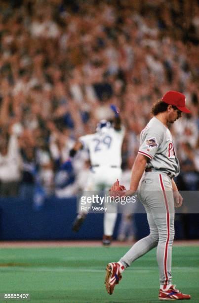 Pitcher Mitch Williams of the Philadelphia Phillies walks off the field as Joe Carter of the Toronto Blue Jays dances his way around the bases after...