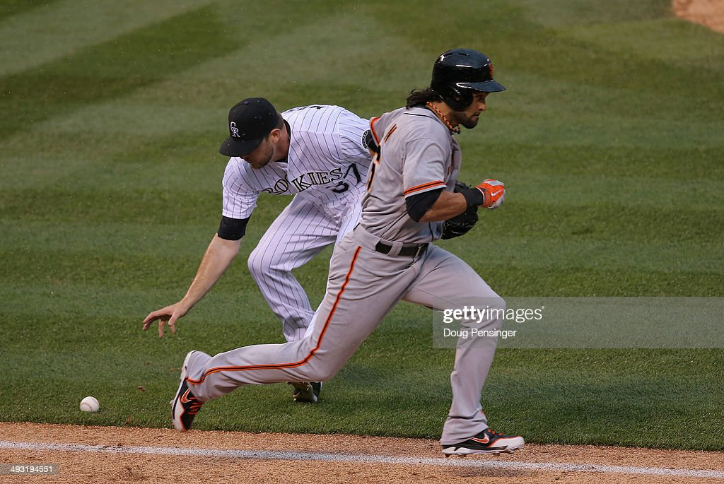 Pitcher <a gi-track='captionPersonalityLinkClicked' href=/galleries/search?phrase=Nick+Masset&family=editorial&specificpeople=2538750 ng-click='$event.stopPropagation()'>Nick Masset</a> #37 of the Colorado Rockies can't handle a soft ground ball as <a gi-track='captionPersonalityLinkClicked' href=/galleries/search?phrase=Angel+Pagan&family=editorial&specificpeople=666596 ng-click='$event.stopPropagation()'>Angel Pagan</a> #16 of the San Francisco Giants singles in the sixth inning at Coors Field on May 22, 2014 in Denver, Colorado.