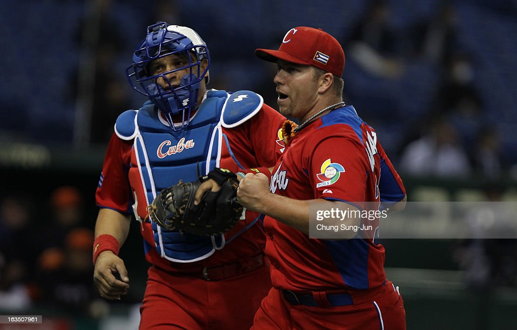 Pitcher Norberto Gonzalez # 33 reacts with catcher Eriel Sanchez # 5 of Cuba after seventh inning during the World Baseball Classic Second Round Pool 1 game between Cuba and the Netherlands at Tokyo Dome on March 11, 2013 in Tokyo, Japan.