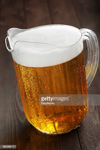 Pitcher of foamy beer on a wooden table