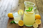 Pitcher of fresh lemonade with filled glass on a rustic wooden background