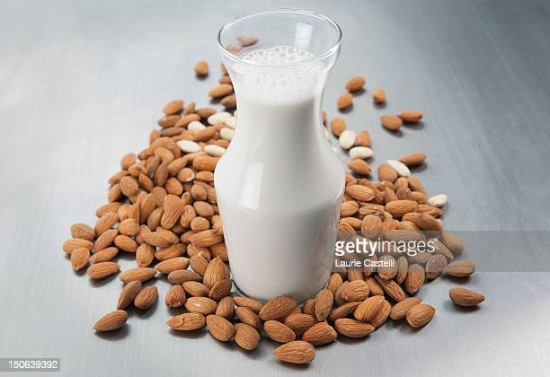 Pitcher of milk and raw almonds