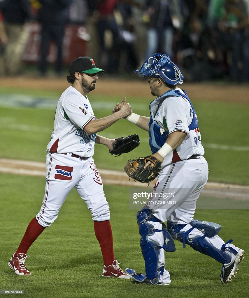 Pitcher Oscar Villarreal (L) and catcher Iker Franco of Yaquis de Obregon of Mexico celebrates victory over Magallanes of Venezuela during the 2013 Caribbean baseball series on February 4, 2013 in Hermosillo, Sonora State, northern Mexico. AFP PHOTO/Ronaldo Schemidt