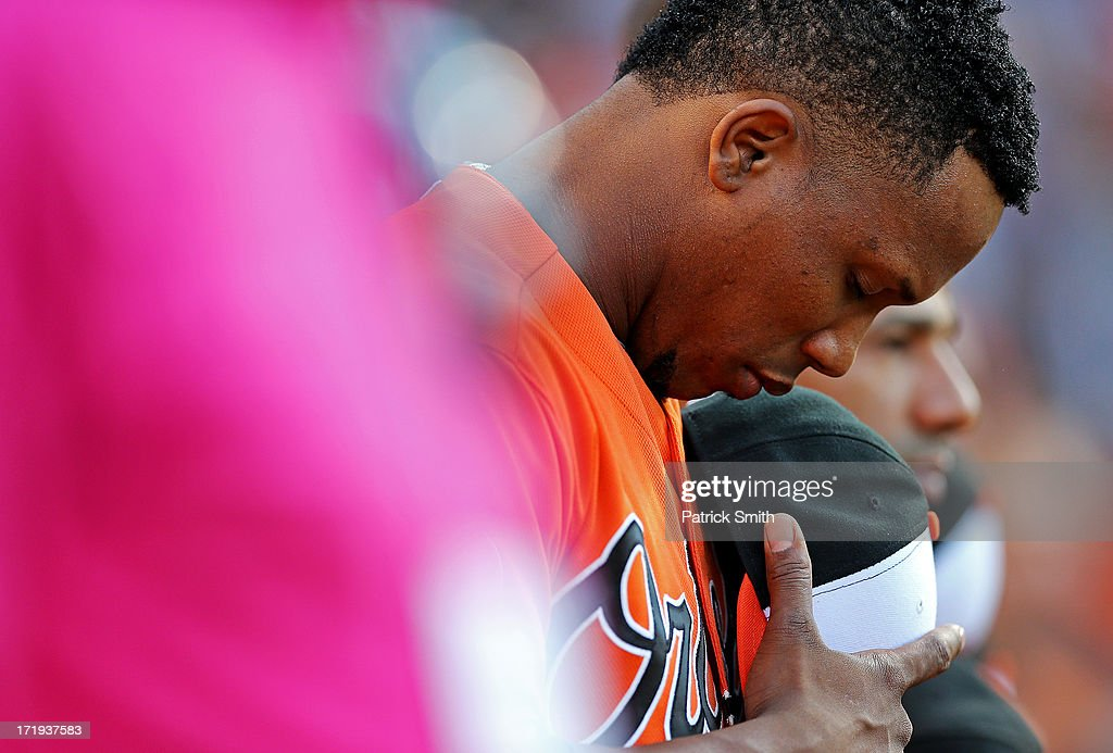 Pitcher Pedro Strop #47 of the Baltimore Orioles has a moment to himself during the national anthem before playing the New York Yankees at Oriole Park at Camden Yards on June 29, 2013 in Baltimore, Maryland.