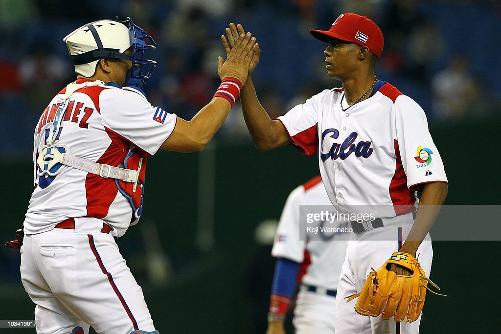 Pitcher Raciel Iglesias #28 (R) and Catcher <a gi-track='captionPersonalityLinkClicked' href=/galleries/search?phrase=Eriel+Sanchez&family=editorial&specificpeople=2948809 ng-click='$event.stopPropagation()'>Eriel Sanchez</a> #5 of Cuba celebrate after winning during the World Baseball Classic Second Round Pool 1 game between Chinese Taipei and Cuba at Tokyo Dome on March 9, 2013 in Tokyo, Japan.