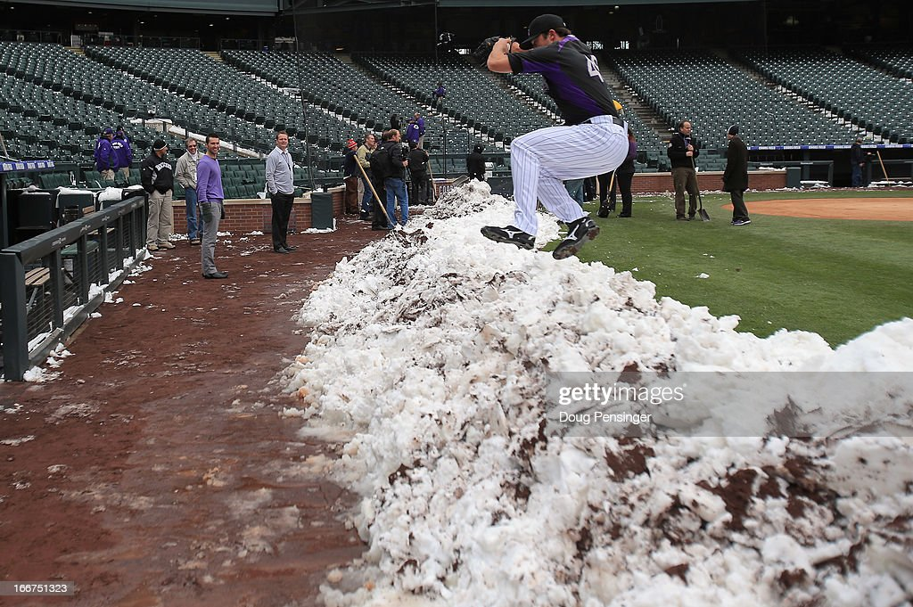 Pitcher Rex Brothers of the Colorado Rockies jumps over a snow bank to get to the dugout as workers remove snow from the field as the New York Mets and the Colorado Rockies prepare for a double header at Coors Field on April 16, 2013 in Denver, Colorado. All uniformed team members are wearing jersey number 42 in honor of Jackie Robinson Day.