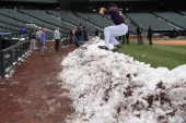 Pitcher Rex Brothers of the Colorado Rockies jumps over a snow bank to get to the dugout as workers remove snow from the field as the New York Mets...