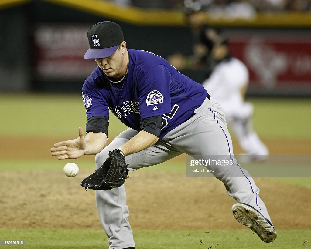 Pitcher Rob Scahill #62 of the Colorado Rockies fields a ground ball by Didi Gregorius #1 of the Arizona Diamondbacks during the sixth inning of a MLB game at Chase Field on September 14, 2013 in Phoenix, Arizona.
