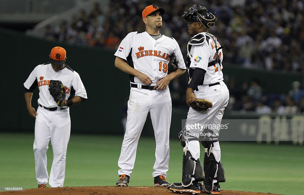 Pitcher Robbie Cordemans # 19 and catcher Dashenko Ricardo # 21 of Netherlands confer in the second inning during the World Baseball Classic Second Round Pool 1 game between Japan and the Netherlands at Tokyo Dome on March 10, 2013 in Tokyo, Japan.