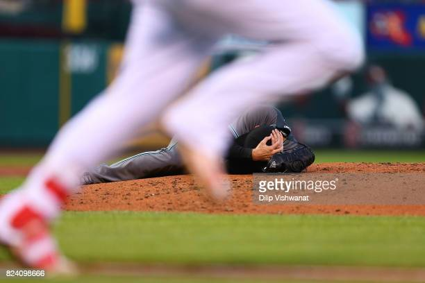 Pitcher Robbie Ray of the Arizona Diamondbacks lays on the pitcher's mound after getting hit in the head by a line drive against the St Louis...