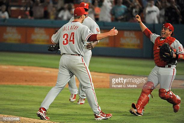 Pitcher Roy Halladay of the Philadelphia Phillies is congratulated by teammates Carlos Ruiz and Ryan Howard after pitching a perfect game against the...