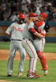 Pitcher Roy Halladay of the Philadelphia Phillies pitches celebrates with teammates Carlos Ruiz and Ryan Howard after pitching a perfect game against...
