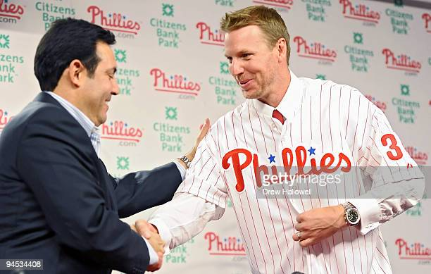 Pitcher Roy Halladay of the Philadelphia Phillies shakes hands with senior vice president and general manager Ruben Amaro Jr after signing with the...