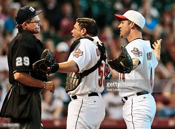 Pitcher Roy Oswalt and catcher Humberto Quintero argue with home plate umpire Bill Hohn after he threw Oswalt out of the game in the third inning...
