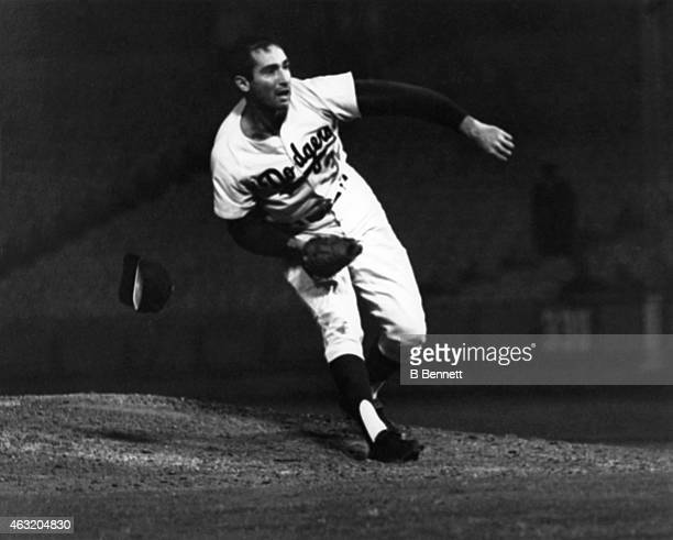 Pitcher Sandy Koufax of the Los Angeles Dodgers throws a pitch as his hat falls off during his perfect game against the Chicago Cubs on September 9...