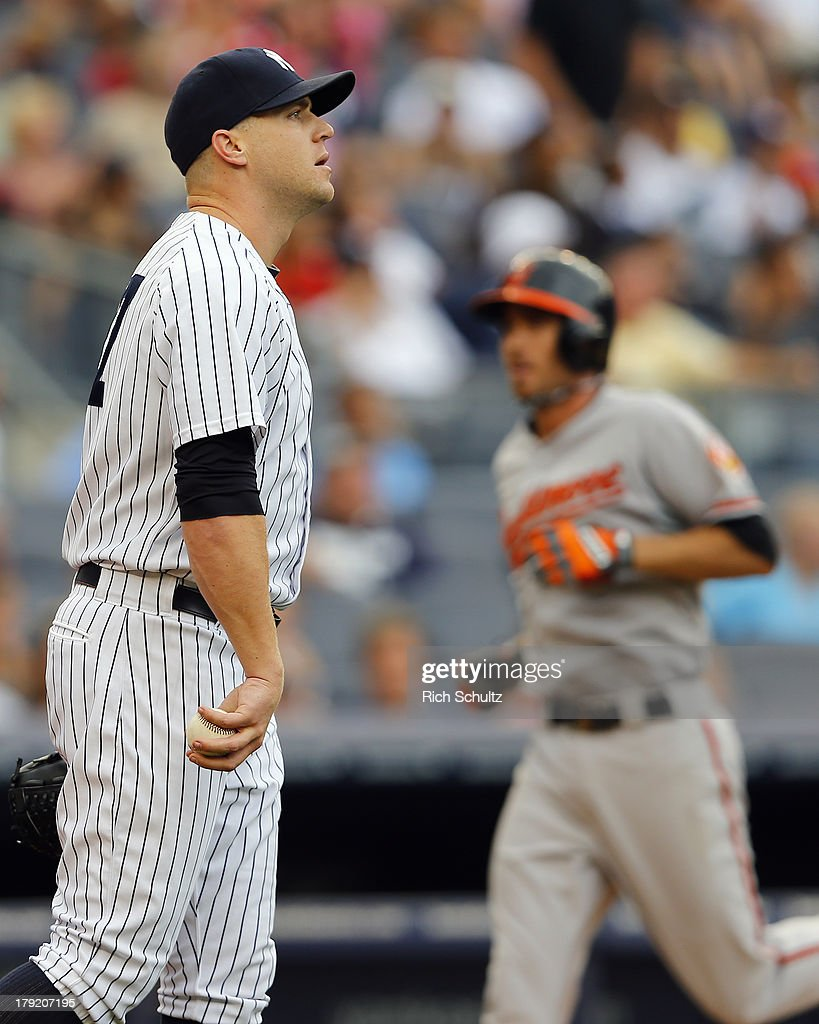 Pitcher Shawn Kelley #27 of the New York Yankees looks away as J.J. Hardy #2 of the Baltimore Orioles crosses the plate after hitting a three run home run in the seventh inning in a MLB baseball game at Yankee Stadium on September 1, 2013 in the Bronx borough of New York City.