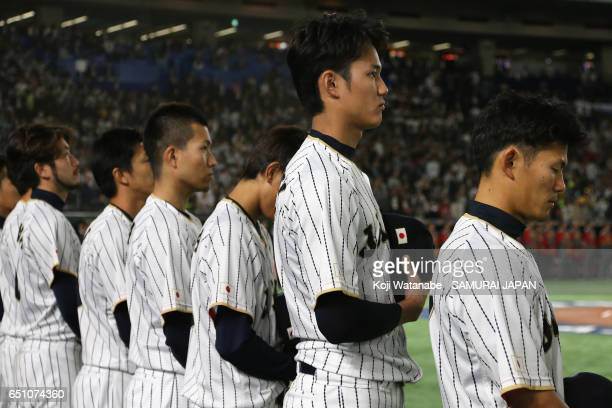 Pitcher Shintaro Fujinami and Japanese players line up for the national anthem prior to the World Baseball Classic Pool B Game Six between China and...