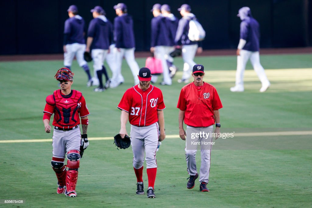 Pitcher Stephen Strasburg #37, catcher Jose Lobaton #59 and pitching coach Mike Maddux of the Washington Nationals walk to the dugout from the bull pen prior to the 1st inning against the San Diego Padres at PETCO Park on August 19, 2017 in San Diego, California.