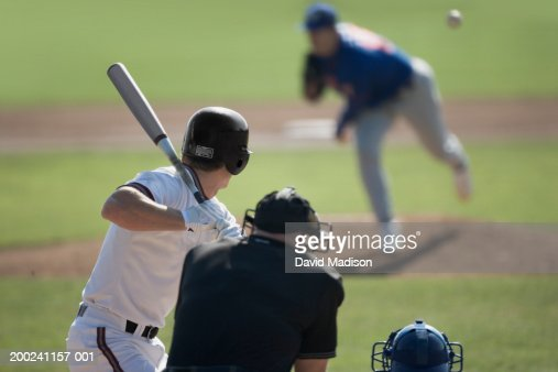 Pitcher throwing pitch to batter, catcher and umpire in foreground : Stock Photo