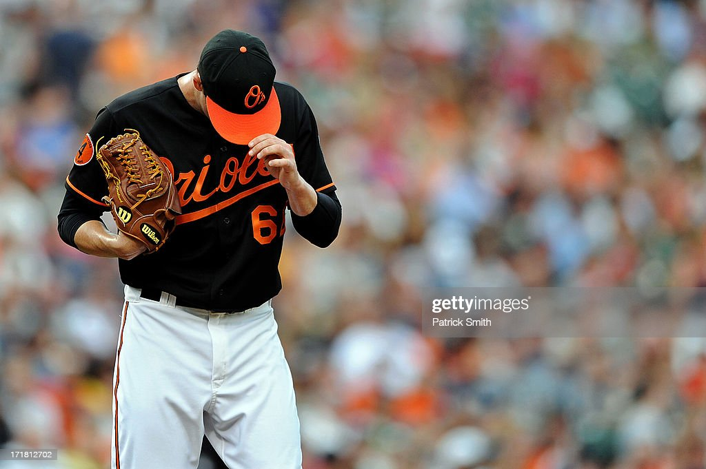 Pitcher T.J. McFarland #66 of the Baltimore Orioles ducks his head after giving up a hit in the second inning against the New York Yankees at Oriole Park at Camden Yards on June 28, 2013 in Baltimore, Maryland.
