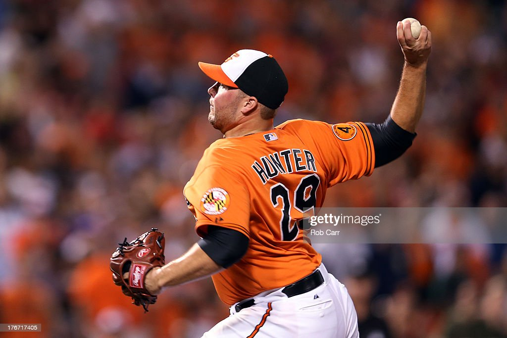 Pitcher Tommy Hunter #29 of the Baltimore Orioles throws to a Colorado Rockies batter during the ninth inning of the Orioles 8-4 win at Oriole Park at Camden Yards on August 17, 2013 in Baltimore, Maryland.