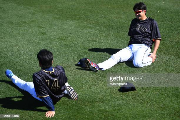 Pitcher Tomoyuki Sugano and Pitcher Takahiro Norimoto of Japan warm up prior to the exhibition game between Japan and Chicago Cubs at Sloan Park on...