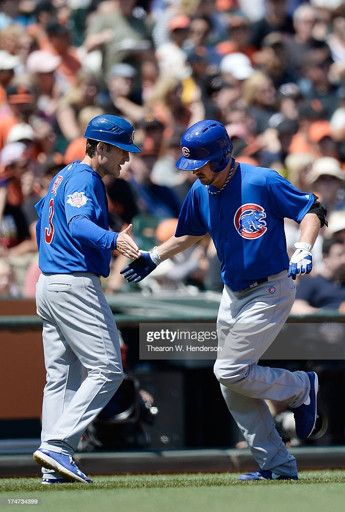 Pitcher Travis Wood #37 of the Chicago Cubs is congratulated by third base coach David Bell after Wood hit a solo home run in the fifth inning against the San Francisco Giants at AT&T Park on July 28, 2013 in San Francisco, California.