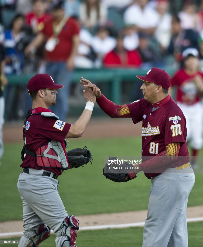 Pitcher Victor Moreno (R) and catcher Jose Yepez (L) of Magallanes of Venezuela celebrate their victory against Criollos de Cagua of Puerto Rico, during the 2013 Baseball Caribbean Series, on February 3, 2013, in Hermosillo, Sonora State, northern Mexico. AFP PHOTO/Ronaldo Schemidt