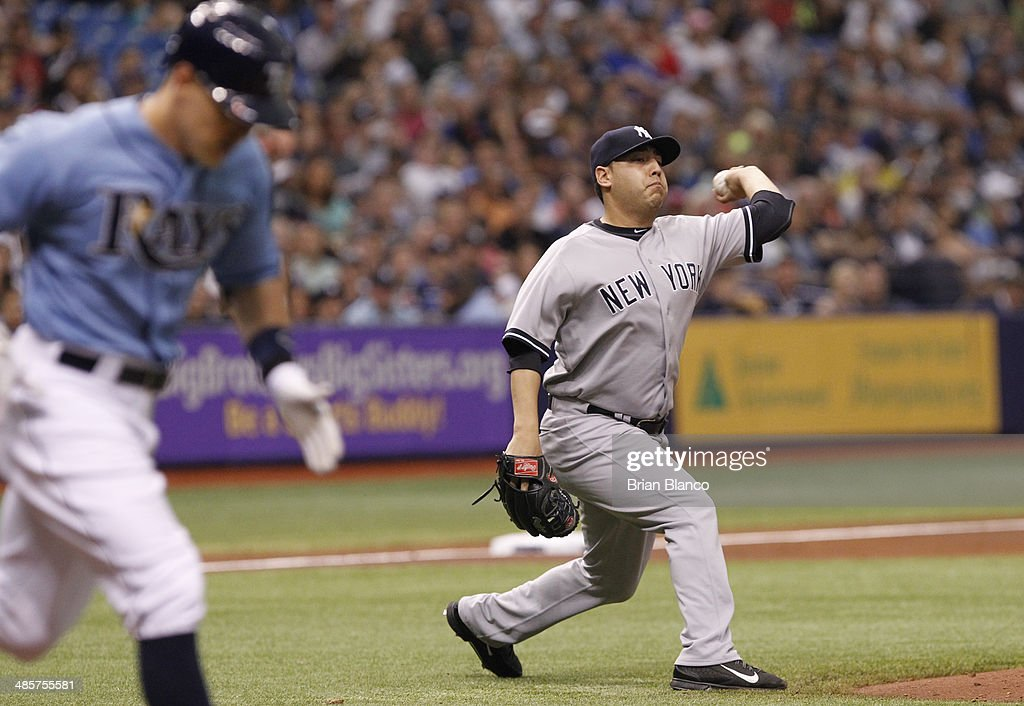 Pitcher Vidal Nuno (R) of the New York Yankees makes the throw to first for the out on Brandon Guyer (L) of the Tampa Bay Rays after Guyer's bunt to the pitcher during the third inning of a game on April 20, 2014 at Tropicana Field in St. Petersburg, Florida.