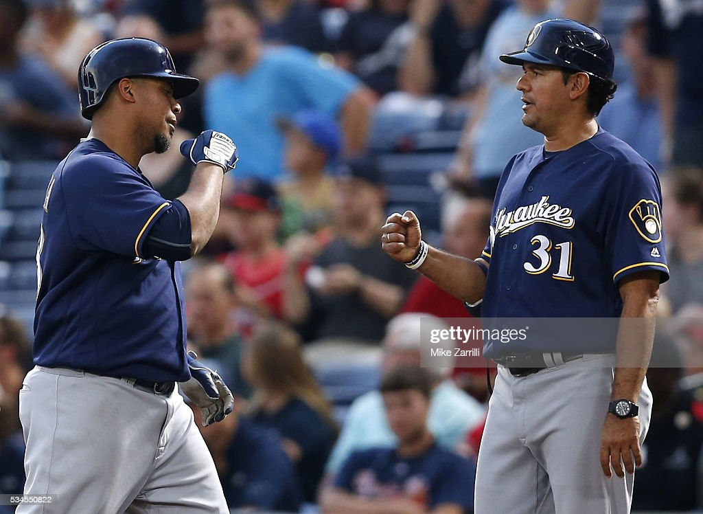 Pitcher <a gi-track='captionPersonalityLinkClicked' href=/galleries/search?phrase=Wily+Peralta&family=editorial&specificpeople=7505871 ng-click='$event.stopPropagation()'>Wily Peralta</a> #38 of the Milwaukee Brewers is congratulated by first base coach Calros Subero #31 after hitting a two-run single in the fourth inning during the game against the Atlanta Braves at Turner Field on May 26, 2016 in Atlanta, Georgia.