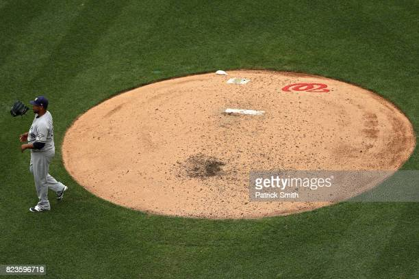 Pitcher Wily Peralta of the Milwaukee Brewers tosses his glove into the air as he walks off of the mound at the end of the fourth inning against the...