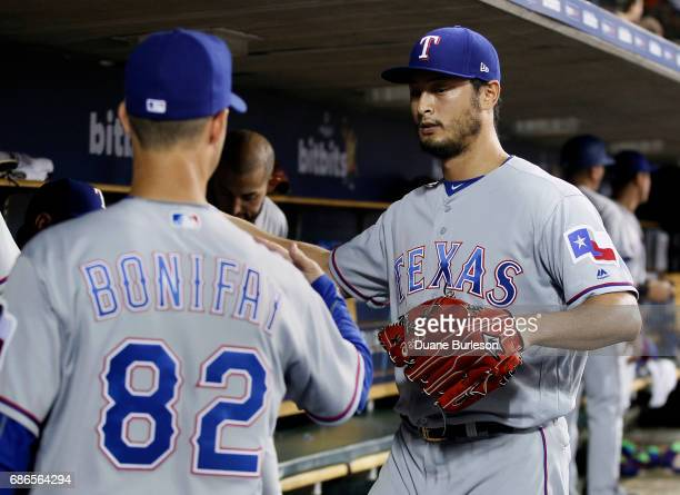 Pitcher Yu Darvish of the Texas Rangers greets field coordinator Josh Bonifay after pitching the fifth inning of a game against the Detroit Tigers at...