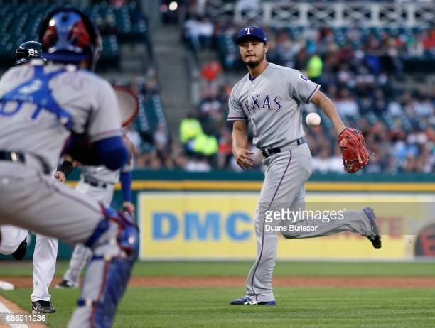 Pitcher Yu Darvish of the Texas Rangers tosses the ball to catcher Robinson Chirinos of the Texas Rangers at home plate to get a force out on Alex...