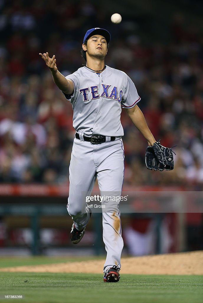Pitcher <a gi-track='captionPersonalityLinkClicked' href=/galleries/search?phrase=Yu+Darvish&family=editorial&specificpeople=4018539 ng-click='$event.stopPropagation()'>Yu Darvish</a> #11 of the Texas Rangers under hands the ball and throws out Mark Trumbo (not pictured) of the Los Angeles Angels of Anaheim in the fourth inning at Angel Stadium of Anaheim on April 24, 2013 in Anaheim, California.