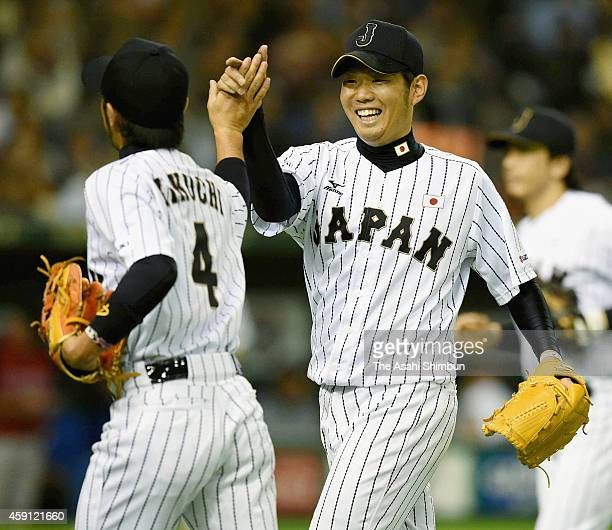 Pitcher Yuki Nishi of Samurai Japan high fives with Ryosuke Kikuchi after the top of 7th inning during the game three of Samurai Japan and MLB All...