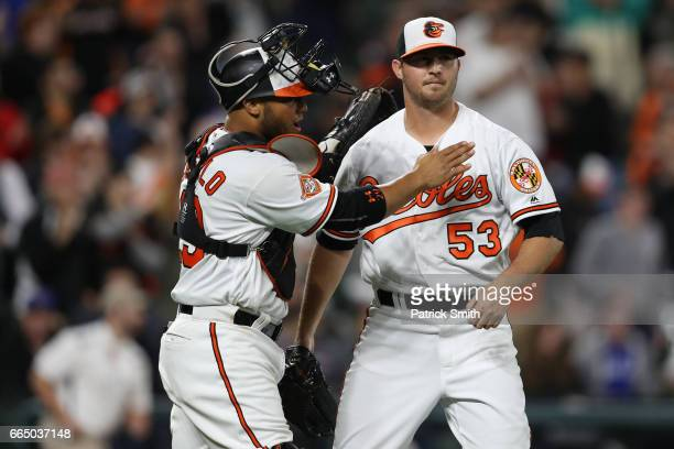 Pitcher Zach Britton of the Baltimore Orioles celebrates with catcher Welington Castillo after defeating the Toronto Blue Jays at Oriole Park at...