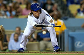 Pitcher Zack Greinke of the Los Angeles Dodgers lays down a sacrifice bunt in the second inning against the Pittsburgh Pirates at Dodger Stadium on...