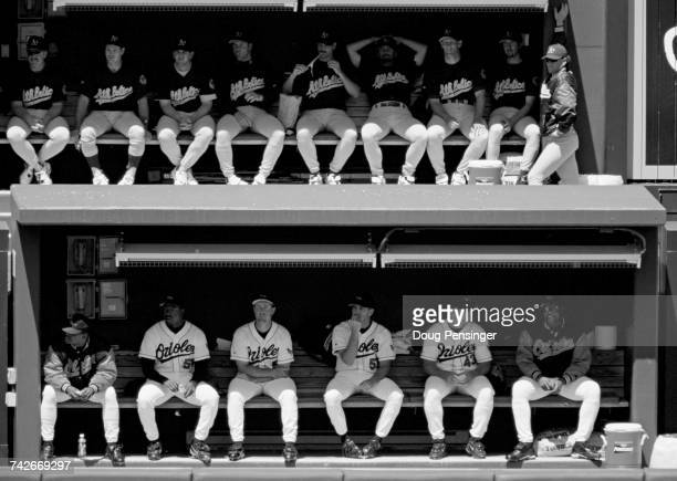 Pitchers and relief pitchers for the Oakland Athletics and the Baltimore Orioles sitting on the bench in the bull pen during their Major League...