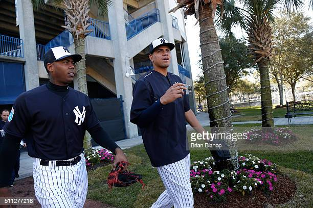 Pitchers Aroldis Chapman left and Dellin Betances of the New York Yankees walk out to the field to participate in a spring training workout on...