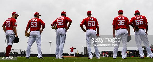 Pitchers keep an eye on Washington Nationals starting pitcher Stephen Strasburg as he takes the mound during morning drills at the Ballpark of the...